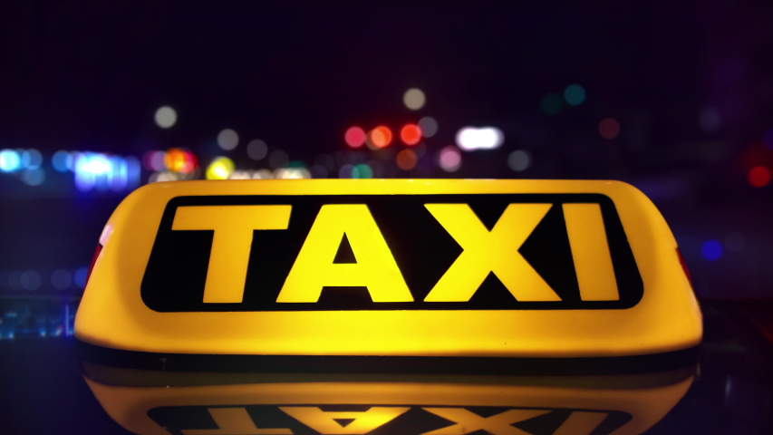 Taxi driving through city at night. Bokeh lights. Detail of the roof light. Timelapse. 4K