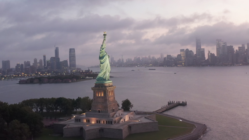AERIAL: Circling Statue of Liberty illuminated in early morning light with foggy New York City Skyline in Background 4K | Shutterstock HD Video #1038761882
