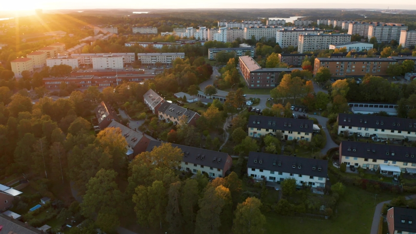 Drone pans over Stockholm suburb during beautiful sunset. Aerial view of houses, Sweden. Royalty-Free Stock Footage #1038766793