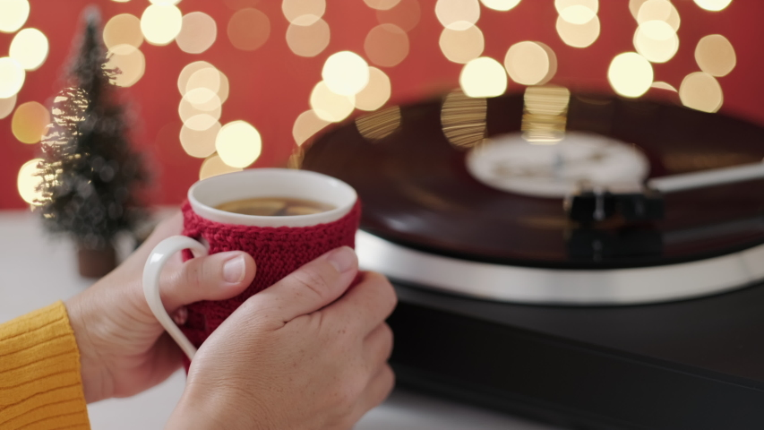 Christmas. Woman holds mug hot tea her hands and warms hands from cold, listening Christmas songs background rotating black vinyl red bokeh Christmas lights. Noel. Popular Disco Trends 70s, 80s, 90s | Shutterstock HD Video #1038777524