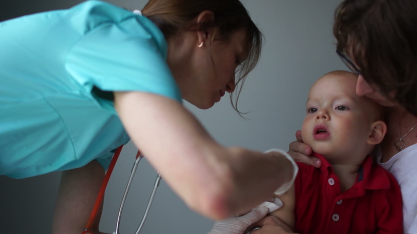 Woman pediatrician gives a flu shot to a baby sitting in the arms of a mother. Close-up. Insulin Injection, Routine Vaccination | Shutterstock HD Video #1038785495