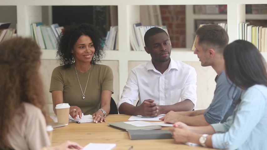 Diverse people sit around boardroom desk negotiating, black woman european man handshake as symbol of successful meeting showing gratitude for work done or express trust for future cooperation concept Royalty-Free Stock Footage #1038796157