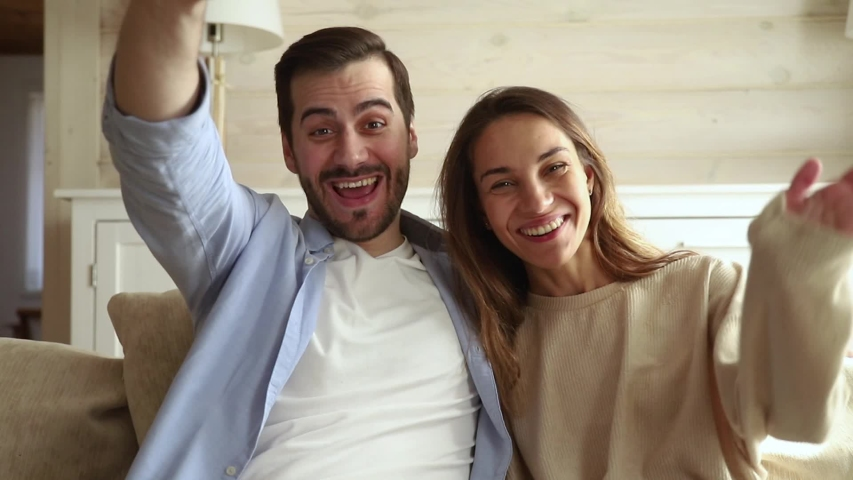 Happy couple make videocall webcam view looking at camera wave hands greeting keep in touch with friends via internet using online application, modern tech users chatting with remote distant relatives Royalty-Free Stock Footage #1038796328