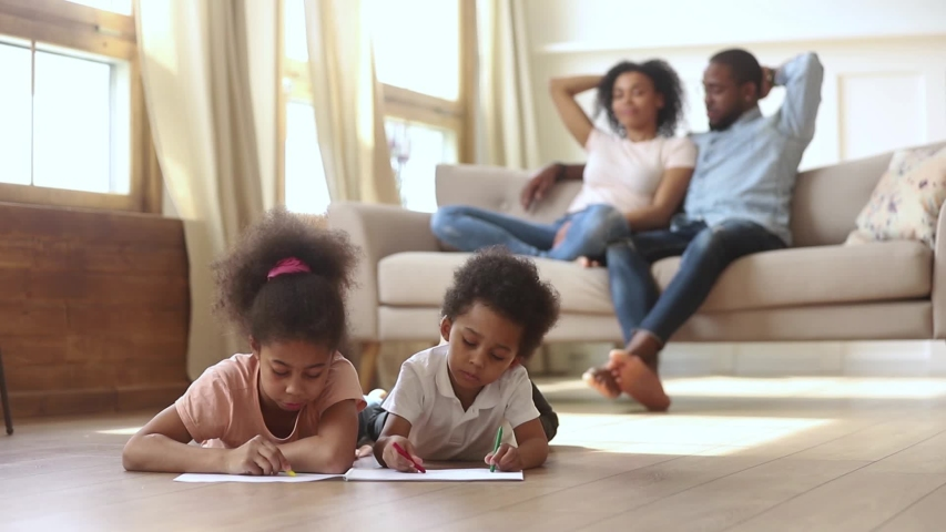 Little mixed race african siblings lying on warm wooden floor in living room drawing with colorful pencils while young black mother and father resting, talking on couch activity at modern home concept #1038796349