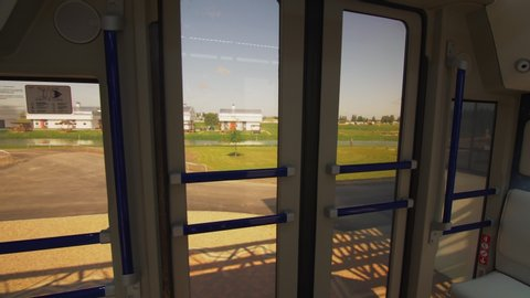 Traveling by new safe unibus vehicle with white benches over green fields at testing ground view from salon on sunny day