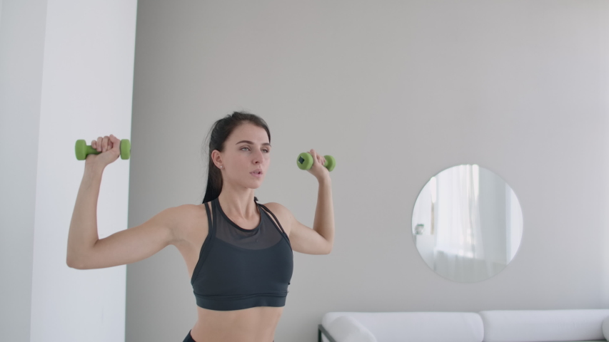 Raise the dumbbells over your head performing exercises for the shoulders. Training at home in the apartment Royalty-Free Stock Footage #1038803318