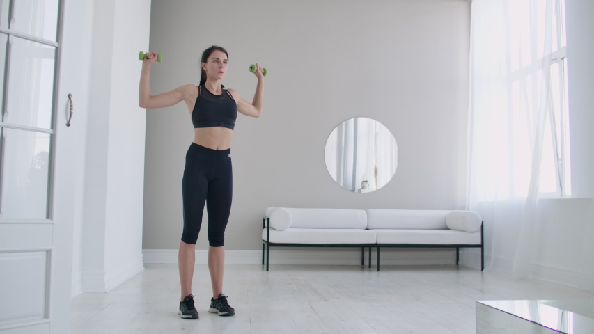 Raise the dumbbells over your head performing exercises for the shoulders. Training at home in the apartment Royalty-Free Stock Footage #1038803330