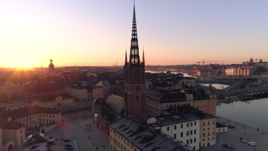 Stockholm downtown city skyline at sunrise aerial view. Drone shot orbiting around church tower building on Riddarholmen island in central Stockholm. Old Town, Gamla stan landmark, Capital of Sweden Royalty-Free Stock Footage #1038809180