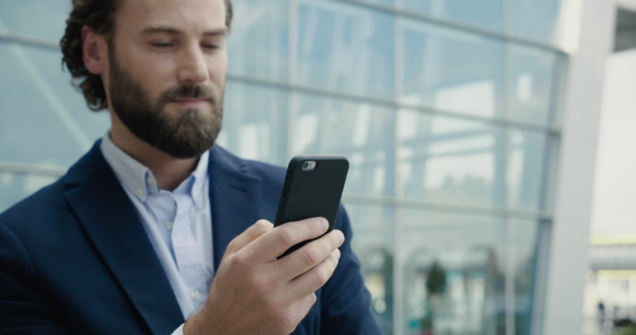 Portrait of Handsome Man is using his Phone after he smiles to the Camera. Attractive Businessman looks charmingly to the Camera. He dressed classical Suit. Smartphones. People. Men. Apps.