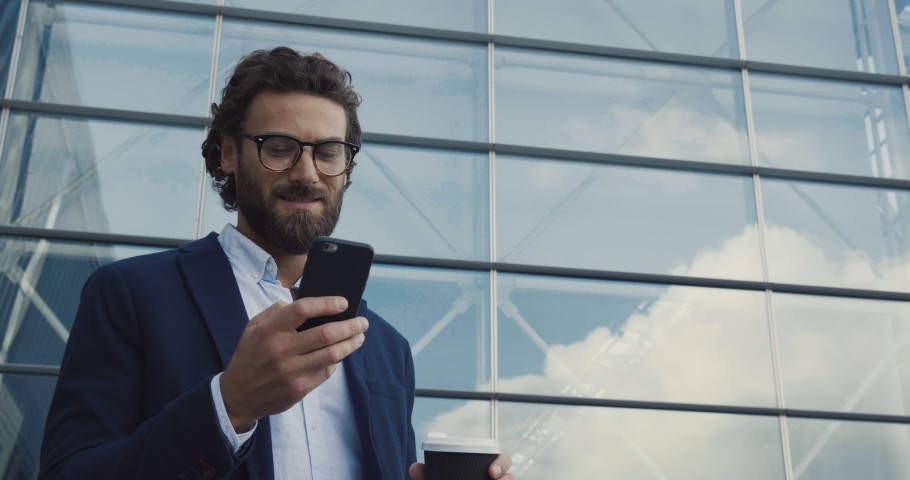 Handsome bearded Startup Businessman in Glasses using mobile Phone. Young man texting Messages, cheating on his Smartphone while walking in Office District. Business. Social Networking. People. Apps.