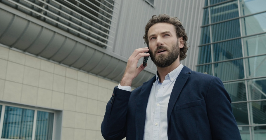 Successful Startupper talking Business-call near modern Business center. Handsome stylish man using his Phone for Business Conversation. Bearded Man walking. Business Lifestyle. People. Man. Apps. Royalty-Free Stock Footage #1038809936