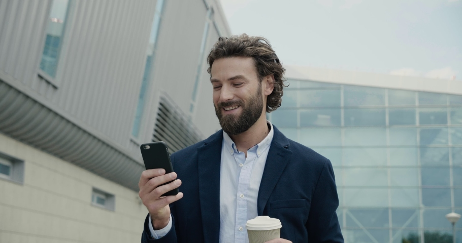 Happy bearded Businessman is texting Messages on his Smartphone and smiles. Young Man is walking near modern Office Building while drinking Coffee to go. Business. Social communication. People. Royalty-Free Stock Footage #1038809960