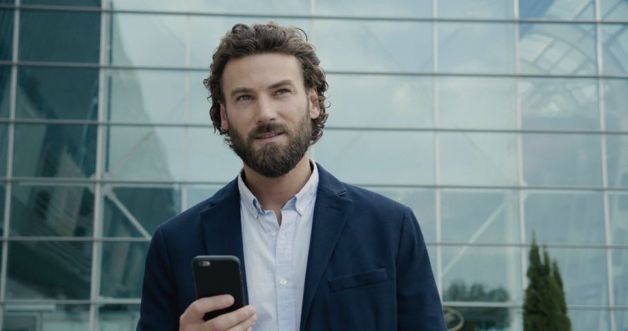 Handsome Man in Smart-casual Suit is walking near modern Office with his Phone. Startup Businessman is watching some Videos on his Smartphone at the Break. Modern Office Worker. Business. Man. Apps. Royalty-Free Stock Footage #1038809969