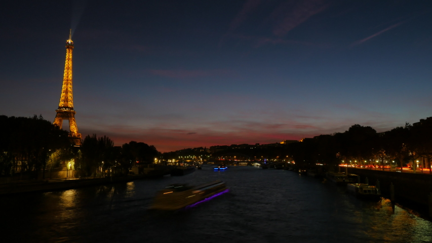 In Paris, the Eiffel Tower lights up and boats traverse the Seine River in time lapse at sundown.   Shutterstock HD Video #1038816440