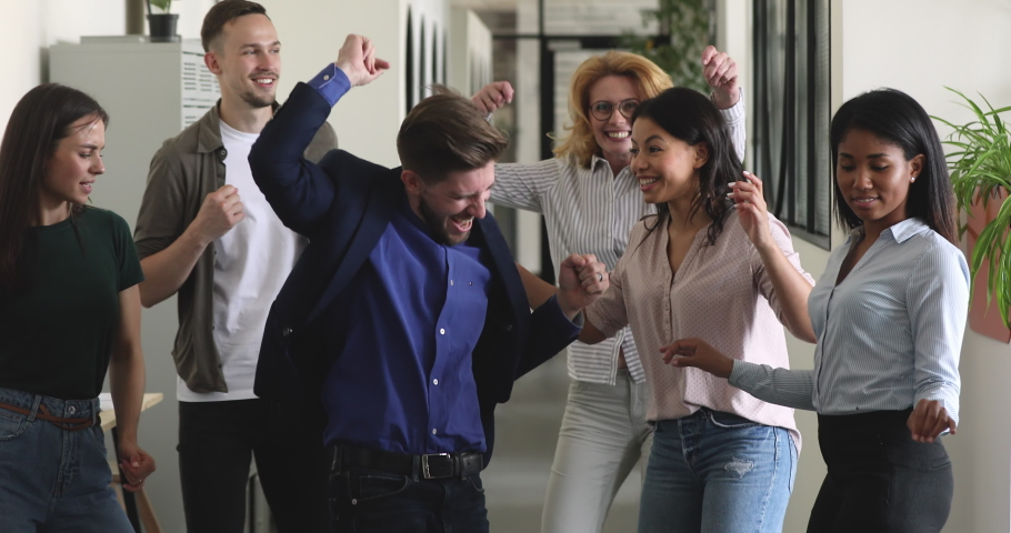 Carefree happy diverse business people with male leader dancing together in office, funny excited multiracial colleagues jumping having fun celebrating success victory enjoy friday corporate party