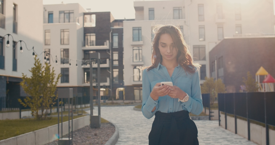 Camera zooming in on the young pretty Caucasian girl who standing in sunlight in the living area in the town among buildings and tapping on the smartphone. Outdoors. | Shutterstock HD Video #1038821891