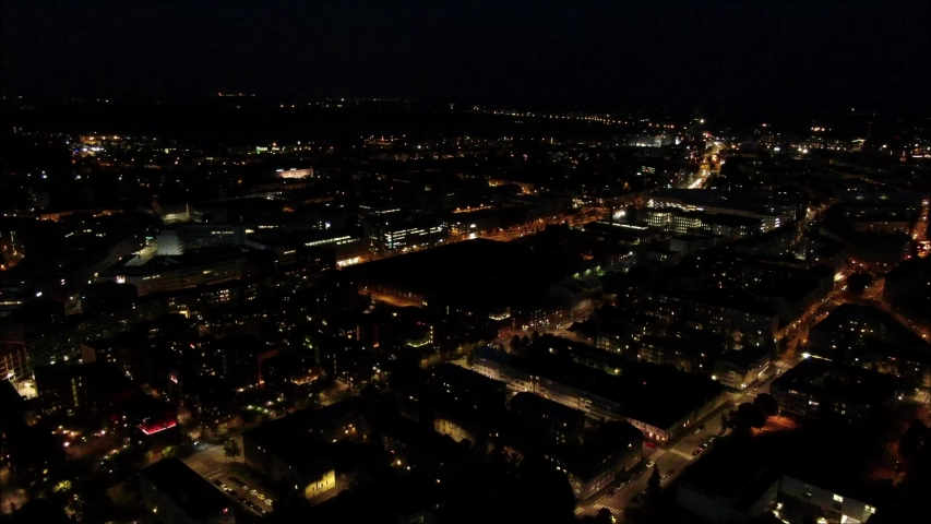 Aerial shot, drone flying forwards over large buildings at night. Illuminated by street lights and building. Helsinki City   Shutterstock HD Video #1038835700