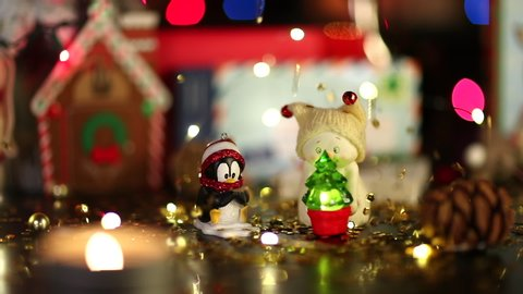 New York. 2019. A festive still life video of Christmas decor under the rain of gold sequins. ?ute penguin toy and little snowman with a small fir are in the foreground.
