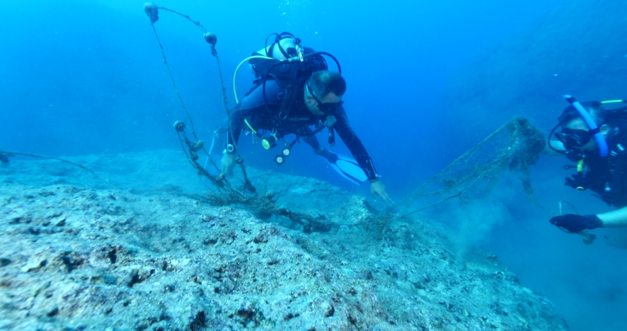 Scuba divers picking old nets and fishing cages underwater ghost hunting dangerous ocean scenery | Shutterstock HD Video #1038845417