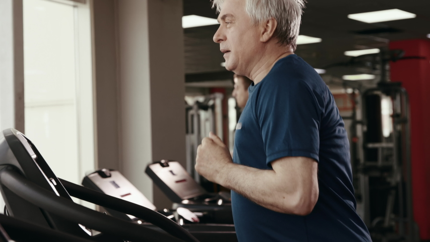 Physical Exercises and Sport Work Out at Gym Room. 50s or 60s Elderly Man Training Healthy Body Close Up. Workout of Old People for Athlete Muscles Inside Fitness Hall. Session of Physical Activity Royalty-Free Stock Footage #1038847325