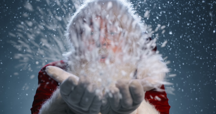 Bearded old man in Santa Claus clothing smiling and blowing snow into camera, isolated over blue background - christmas spirit concept close up 4k footage