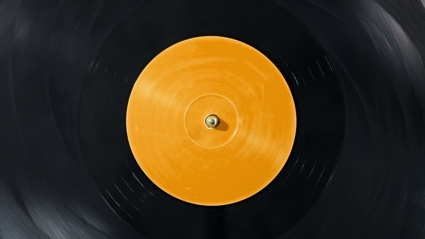 Black vinyl Retro record on DJ turntable. Black vinyl background with yellow screen in center. Rotating plate close up. Party. Loop. Macro View from above Popular Disco Trends 60s, 70s, 80s, 90s