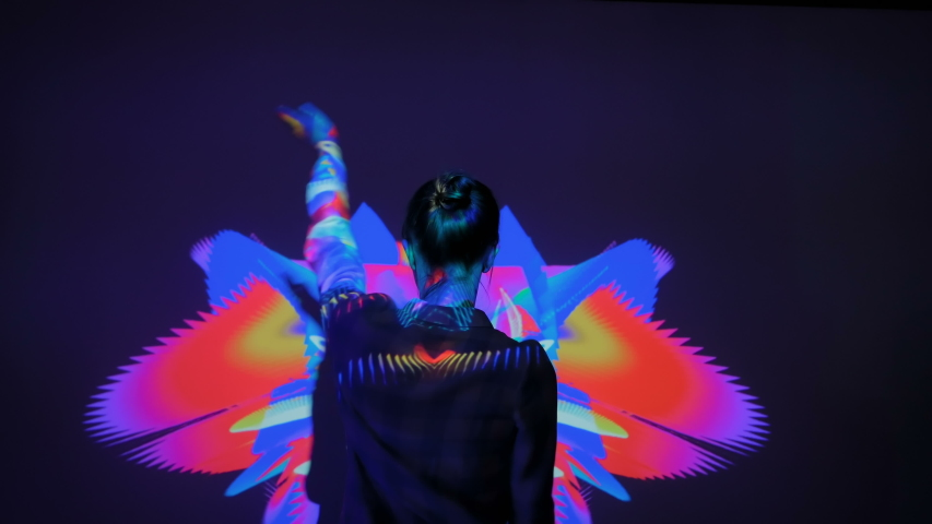 MOSCOW, RUSSIA - MARCH 1, 2019: Large screen augmented reality experience - woman waving arms and dancing in front of wall display with mirror effect at modern AR futuristic immersive exhibition