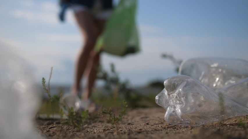 Plastic pollution of nature. Volunteer picking up trash on the beach. | Shutterstock HD Video #1038911201