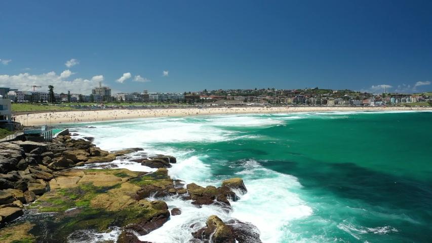 Sydney, Australia. Bondi beach, reveal drone video clip. Beautiful sunny day, big Pacific Ocean waves hitting the rocks. Stunning clear blue ocean water. Most popular white sand beach in Sydney.