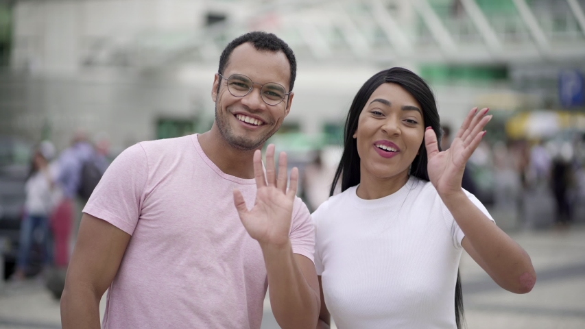 Happy young people talking to camera. Smiling multiracial couple standing on street and waving to camera. Concept of storytelling | Shutterstock HD Video #1038917273