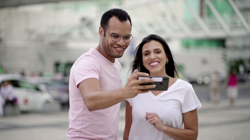 Cheerful young couple recording video message. Smiling young man holding smartphone in outstretched arm and talking. Communication and technology concept   Shutterstock HD Video #1038917327