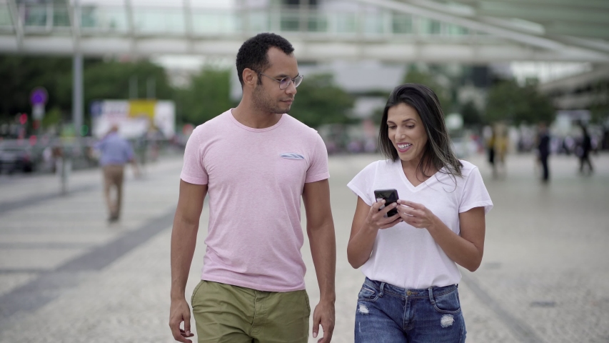 Front view of good friends walking on street and talking. Smiling multiracial colleagues looking at smartphone during stroll on street. Communication and technology concept    Shutterstock HD Video #1038917333