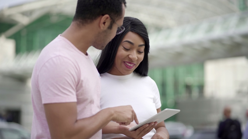 Joyful friends standing on street and using tablet. Cheerful young people talking while looking at tablet. Communication and technology concept | Shutterstock HD Video #1038917363
