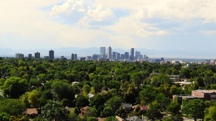 Aerial: Denver Skyline on Sunny Day Over Richly Forested Neighborhoods - Denver, Colorado