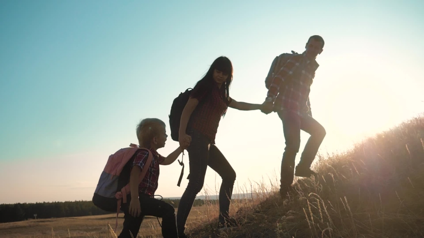 Teamwork hikers help business travel silhouette concept. group of tourists happy family lends a helping hand climb the cliffs mountains. people mom dad and son little boy climbers teamwork climb to | Shutterstock HD Video #1038944732