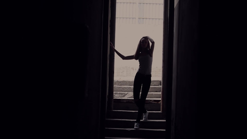 Girl posing in the shadow of a narrow passage | Shutterstock HD Video #1038951179