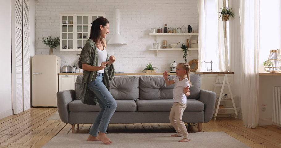 Funny cute small kid daughter copy imitate carefree young mom dancing together at home, happy family single mother and active little child girl having fun enjoy funny dance in modern kitchen interior | Shutterstock HD Video #1038952523