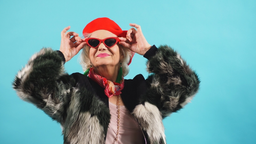 Optimistic old woman doesn't think about her age, oldness. Isolated blue background. lifestyle, leisure. happiness | Shutterstock HD Video #1038953273