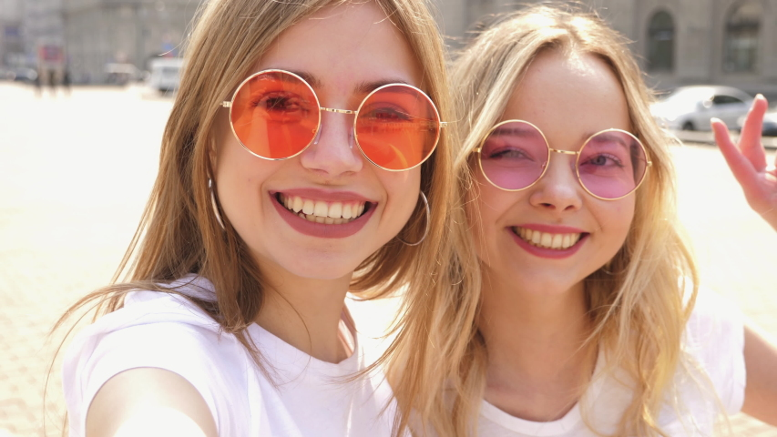 Two young smiling hipster blond women in summer white t-shirt clothes. Girls taking selfie self portrait photos on smartphone.Models posing on street background.Female showing positive face emotions | Shutterstock HD Video #1038954302