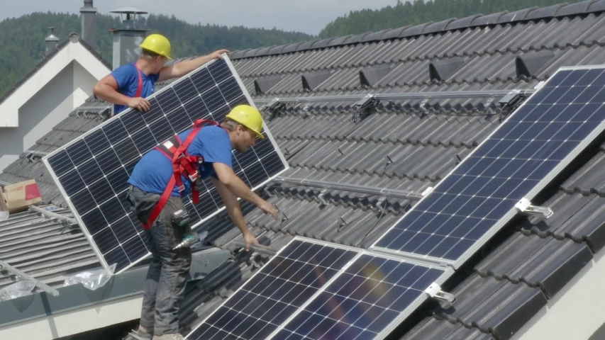 Workers installing PV (Photovoltaic) solar panels on the roof of a house,which converts solar energy into electric energy.A static footage.Concept of job,work,duty,professionalism.(2) | Shutterstock HD Video #1038958526