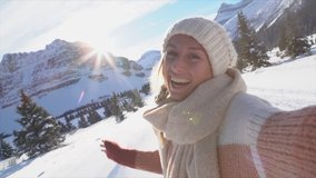 Young woman on a winter vacation takes a selfie surrounded by snowy landscape. Woman travelling in Canada during Christmas season takes a video selfie. Slow motion
