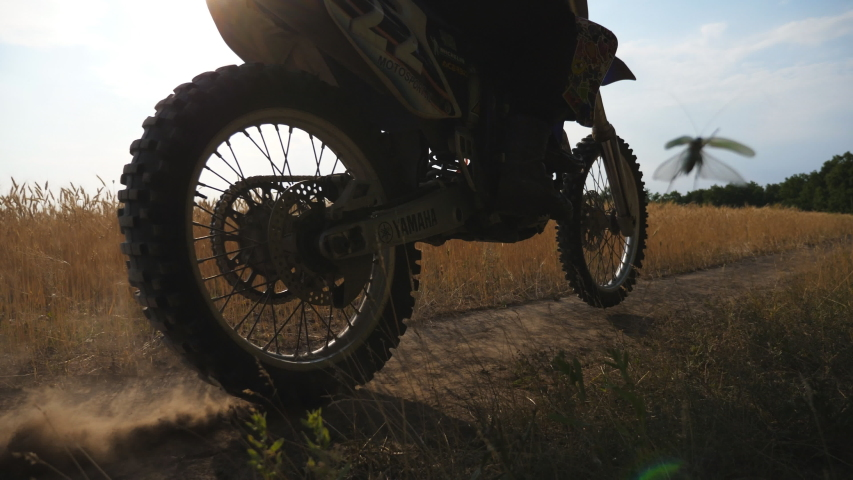 Young motorcyclist driving on road near wheat field. Male driver riding at motocross on trail near barley meadow. Biker having active rest on nature. Concept of extreme sport. Rear view Slow motion | Shutterstock HD Video #1038970736