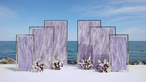 stylish wedding site arch decorated with white and purple flowers against endless blue sea on summer day slow motion