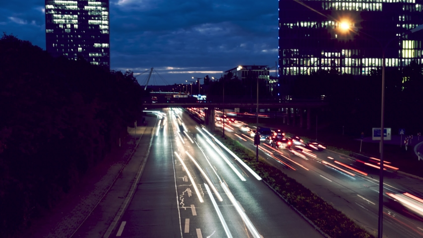 Timelapse of car traffic jam at busy street road highway long exposure light trails during dark evening night with munich skyline background