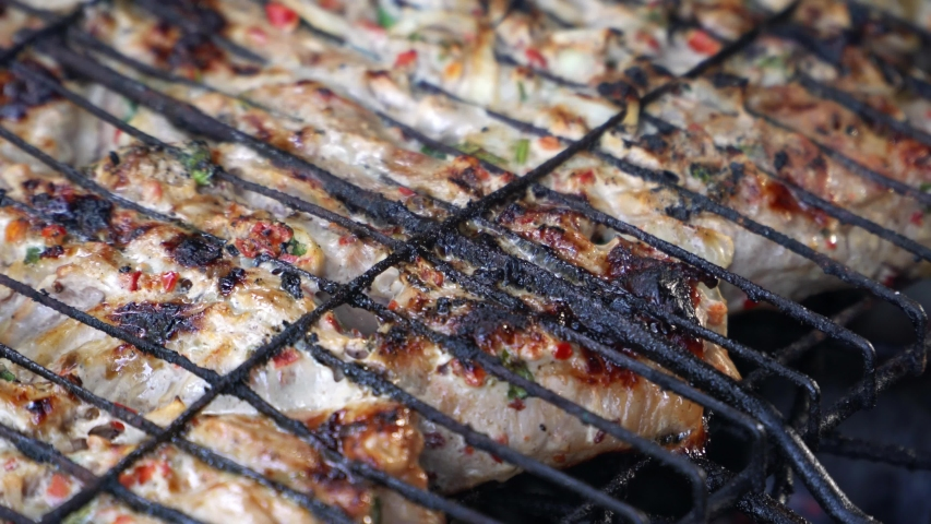 The meat is roasted on a grill on coals | Shutterstock HD Video #1038977504