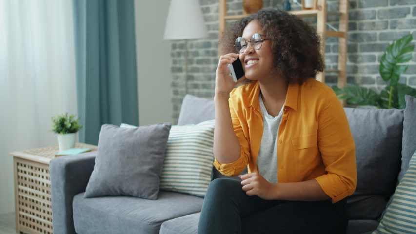 Slow motion of young African American woman laughing talking on mobile phone at home sitting on couch in apartment. People and communication concept. | Shutterstock HD Video #1038994196