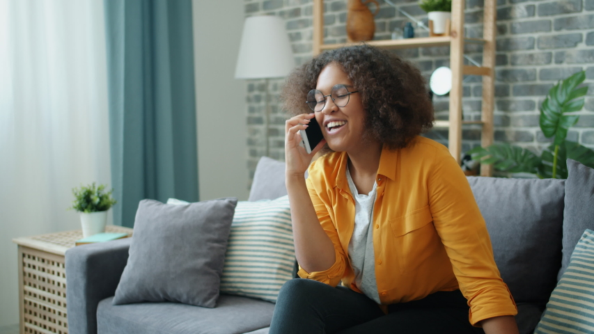 Cheerful young African American lady is speaking on mobile phone in apartment laughing gesturing having fun indoors. Communication and happy youth concept. | Shutterstock HD Video #1038994199