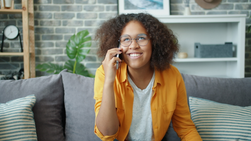Joyful African American teenager is chatting on mobile phone at home laughing enjoying communication sitting on couch alone. People and modern devices concept. | Shutterstock HD Video #1038994202