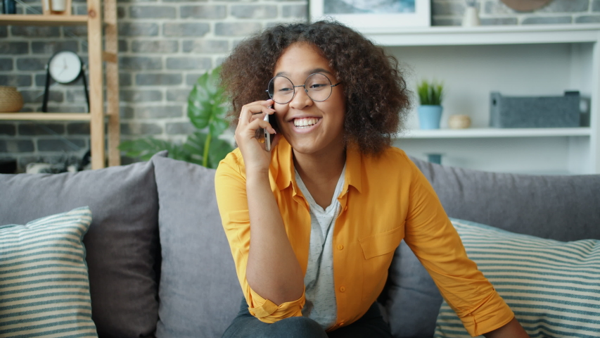 Good-looking African American girl is talking on mobile phone smiling and laughing sitting on sofa in beautiful modern apartment. Gadgets and communication concept. | Shutterstock HD Video #1038994205