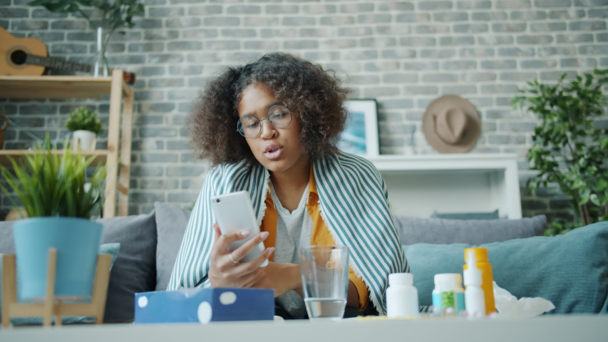 Sick young woman student is talking online with doctor getting video consultation showing pills on smartphone sitting on couch under blanket. People and gadgets concept. | Shutterstock HD Video #1038994250